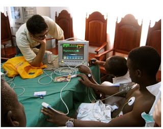Dhairya Pujara (at left) testing medical equipment at the Chicque Rural Hospital in Mozambique.