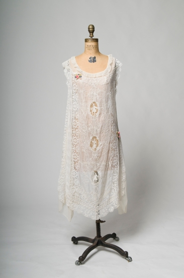 A day dress from the French couture house of Boue Soeurs, purchased at their New York branch circa 1925. It is a soft and romantic summer day dress of white cotton and lace trimmed with roses of ribbon embroidery. It would have been perfect for a garden party on a grand Long Island estate.