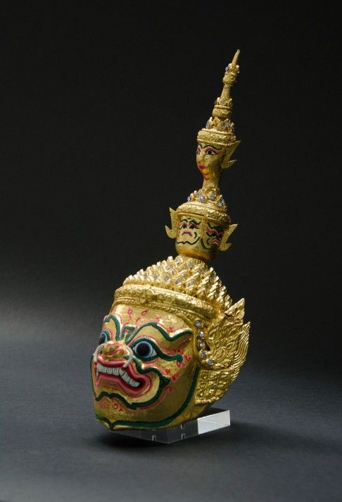 A mask from Bangkok, Thailand made of decorative gilt with inlay of stones.