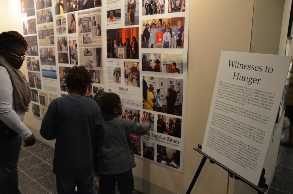 Tianna Gaines-Turner, a Witness to Hunger from Philadelphia, shows her children an action wall depicting Witnesses' experiences speaking in public, with legislators and through the media.