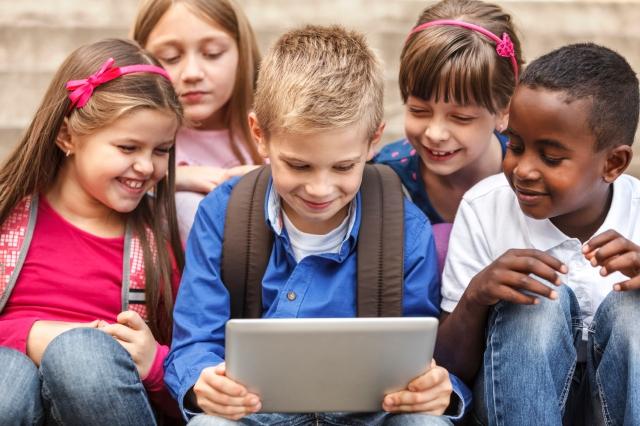 School children using digital tablet outside