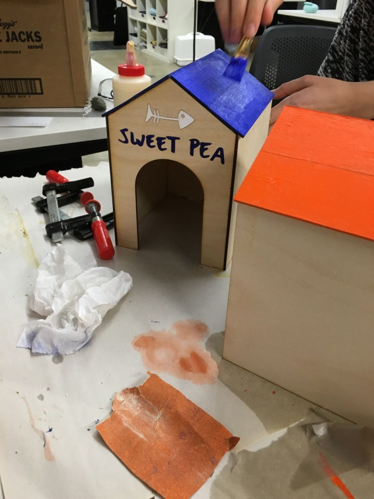 "Junior product design student Gina Lerman paints houses that 3D printed cats and dogs will come out of and race down the track in the ""Dog vs. Cats a Race for Love"" project."