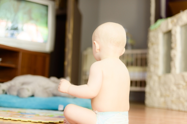naked baby watching TV sitting on the floor?? in a diaper