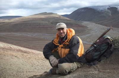 Ted Daeschler sitting on a hillside next to his gear.