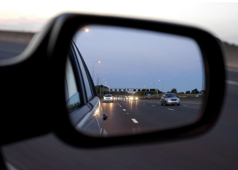 A car's sideview mirror with a view of the highway and other cars