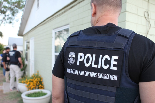 Immigration and Customs Enforcement officer looking on during a raid.