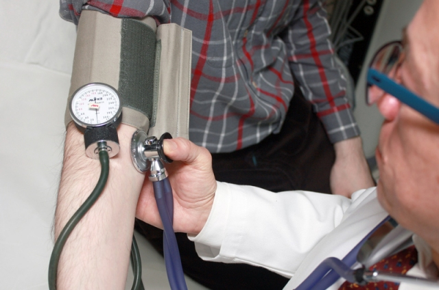 A doctor taking a patient's blood pressure with an arm cuff