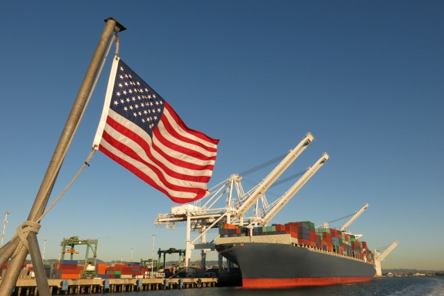 An American flag waves in the foreground at this US port, where a cargo ship loaded with containers is berthed beneath giant cranes on a clear blue sky day.