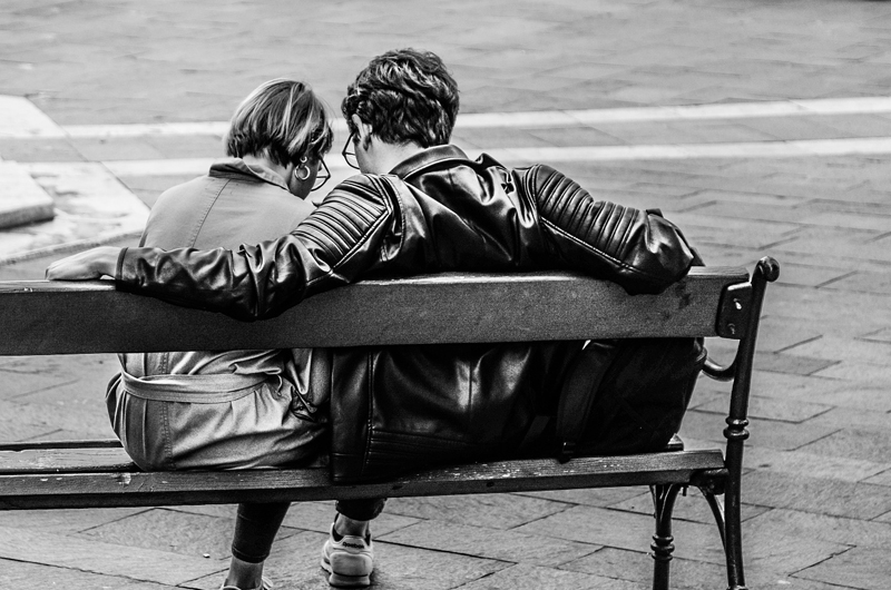 Two people sitting together on a bench