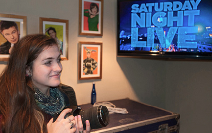 Student with camera in front of a TV screen that says Saturday Night Live