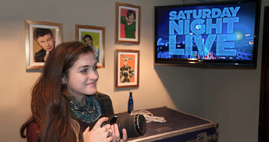 Student in front of a TV screen with a camera that says Saturday Night Live