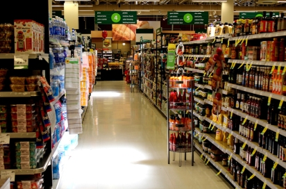 Looking down the aisle of a grocery store with full shelves.