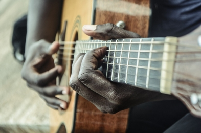 A close-up of the hands of a person playing an acoustic guitar