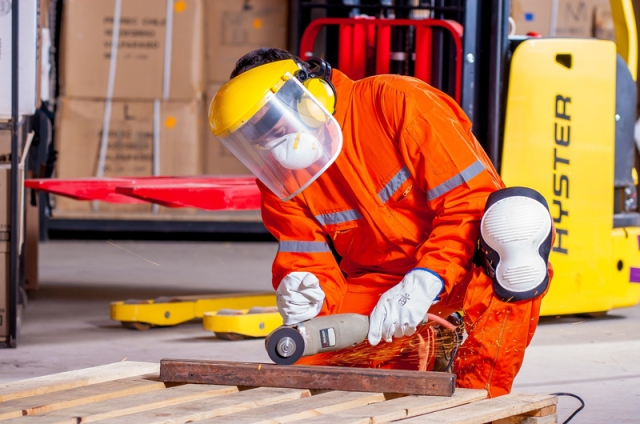 A worker with a grinder wearing protective gear.