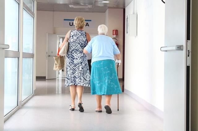 A woman escorting an older woman downa hallway