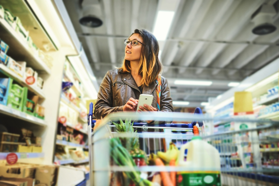 woman shopping in a grocery store with a list on her smartphone